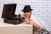 woman in a hat listening to records on the gramophone