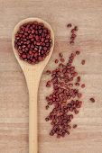 Adzuki beans in a wooden spoon over papyrus background.