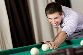 Young man playing billiard. Spending free time on gambling