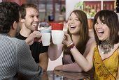 Jóvenes amigos brindando con tazas de café
