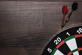 target and two darts over brown wooden table background