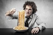young businessman eating spaghetti