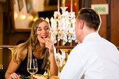 Couple - man and woman - in a fine dining restaurant they eat fast food and fries - a large chandeli
