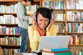 Student - Young woman in library with laptop and headphones learning, a male student standing in the