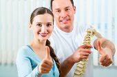 Physiotherapist and patient in a practice after a successfully treatment is the diagnosis a clear improvement, thumbs up