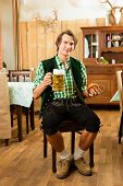 picture of stein  - Young man in traditional Bavarian Tracht in restaurant or pub with beer and steins and pretzel - JPG