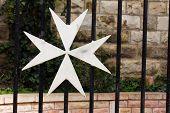 picture of maltese-cross  - White Maltese cross on  a black metal fence - JPG