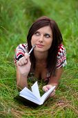 Beautiful Brunette Girl With Notebook And Pen Lying On The Grass