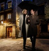 stock photo of overcoats  - Elegant couple in autumnal coats walking in the rain outdoors at night - JPG