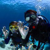 Scuba divers underwater showing ok signal