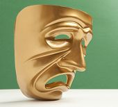 Tragedy theatrical mask on a green background
