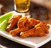 stock photo of dipping  - buffalo chicken wings with beer - JPG