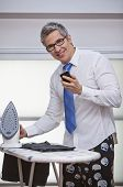 Businessman Text Messaging On A Mobile Phone While Ironing Pants