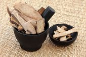 Peony root used in chinese herbal medicine in a black stone mortar with pestle and bowl over wicker.