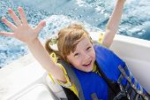 stock photo of boat  - Two kids sitting in the bow of a boat with there life jackets having fun - JPG