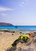 Scuba Mask And Snorkel On The Rock With Blue Sea In Background