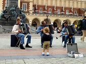 Krakow, Poland - June 27: A Child Diligently Observing And Admiring Street Team Plays Accordion On T