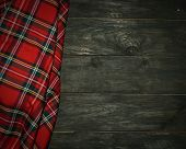 picture of kilt  - tartan textile on old wooden scratched background - JPG