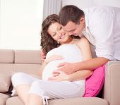 Happy Couple Expecting Baby. Beautiful Young Pregnant Woman and Her Husband Together Caressing Her Pregnant Belly at Home on a Sofa. Mom and Dad