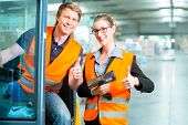 Logistics Teamwork - forklift driver, Worker or warehouseman and his coworker with scanner at wareho