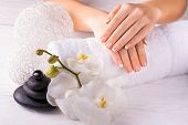 Beautiful hands with manicure and wnite orchid flower