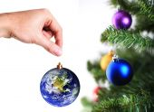 Hand Hanging Up Earth Decoration On Christmas Tree