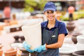smiling hardware store worker holding clay plant pot