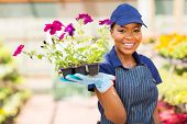 happy african nursery worker holding flowers in greenhouse
