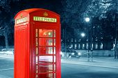 Red Telephone Booth in street at night in London.
