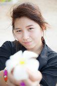 Asian Women Black Shirt. Holding White Flower.