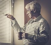 image of jalousie  - Senior man with cup looking out the window through jalousie - JPG