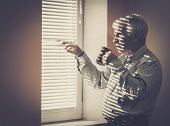 stock photo of jalousie  - Senior man with cup looking out the window through jalousie - JPG