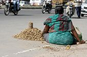 Poor indian street vendor sell peanuts on a busy road