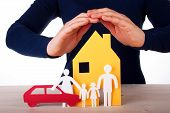 stock photo of loneliness  - Two Hands are Protecting a Family infront of its House with their Car Isolated - JPG