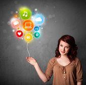 Pretty young woman holding colorful social media icons balloon