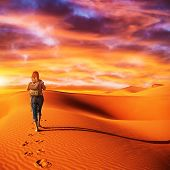 Traveler in the desert, active young woman trekking in hot sandy wilderness, dramatic sunset, summer