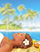 Beautiful African woman sleeping on massage table on the beach, enjoying day spa, luxury summer vaca