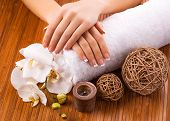 french manicure with white orchid  on a bamboo background
