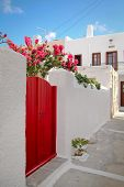 Nice red door on a white wall at Milos island Greece