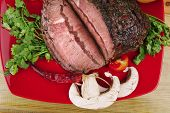 fresh red hot barbecue beef meat on plate served with green salad and vegetables over wooden table