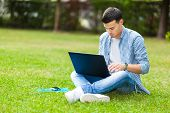 Student using a laptop on the grass at the park