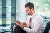 Happy businessman in office with tablet