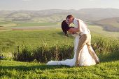 stock photo of zulu  - Bride and groom outside garden wedding with African Natal Midlands mountain scenery background - JPG
