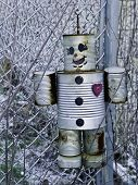 pic of scarecrow  - A model robot made of tin cans haning on a fence as a scarecrow - JPG