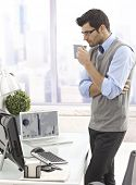 Businessman standing by desk, drinking coffee, looking at computer screen.