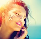 stock photo of sunbathing woman  - Suntan Lotion Woman Applying Sunscreen Solar Cream - JPG