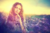 Beauty Girl Portrait. Sensual Woman Lying on a Meadow with Violet Flowers. Beautiful Woman Enjoying Nature. Romantic beauty in fantasy lavender field