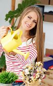 Lifestyle. Cute, attractive woman with watering can