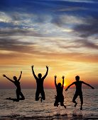 pic of gravity  - silhouette of jumping people on sunset background - JPG
