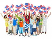 Cheerful Multi-Ethnic Group Of People Standing With Their Arms Raised Holding American Flag.